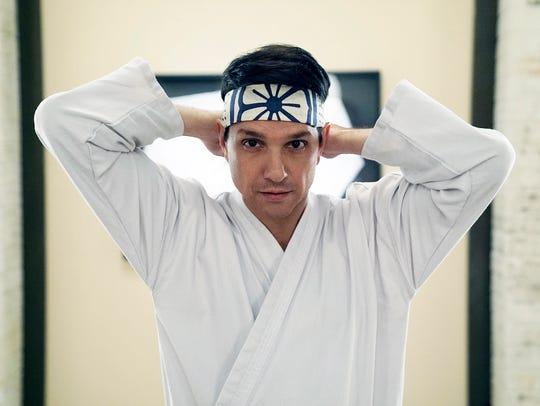 "Ralph Macchio dons familiar headwear as Daniel LaRusso in ""Cobra Kai,"" YouTube Premium's continuation of the ""Karate Kid"" movies."