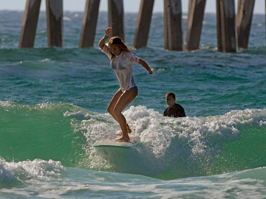 Abigail Renke takes to the surf Saturday during the Innerlight Surf Shop's fourth annual Yancy Spencer III Memorial Surf Contest at Pensacola Beach.