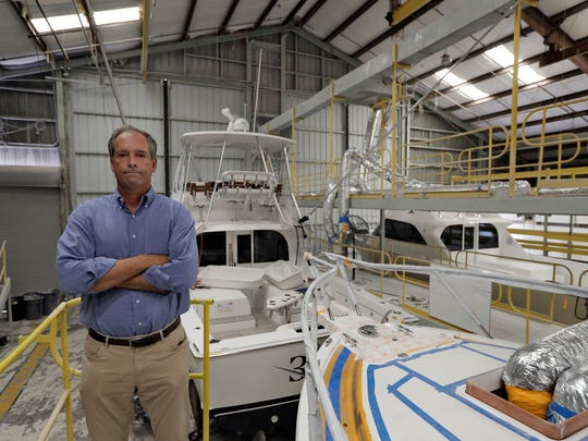 Peter Truslow, Chief Executive Officer for Bertram, a boat building company, poses near three of his custom made boats Friday.