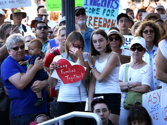 Shalise Ptak, middle, becomes emotional during the Families Belong Together rally in downtown Reno on June 30, 2018.