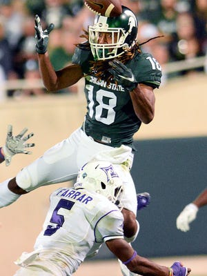Michigan State University  sophomore receiver Felton Davis III (18) goes up to try and catch a Tyler O'Connor pass in the second half of play against Furman in the Spartan's opening game of the 2016 season Friday, Sept. 2, 2016, in East Lansing. Davis wouldn't be able to make the reception and was injured on the play. He finished the game with three catches for 40 yards and a touchdown.