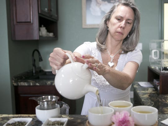 Owner Judy Van Berkel pours white teas into a cup at