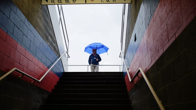 An usher braves the rain before the scheduled start time of the Binghamton Mets opening game against the New Hampshire Fisher Cats at NYSEG Stadium on Thursday, April 7, 2016. The game was postponed due to rain.