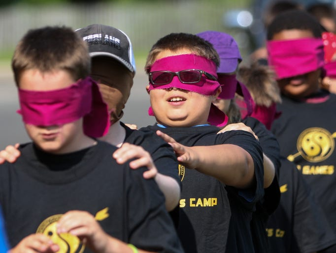 Eatontown,  NJ      Hunger Games Camp through the Monmouth County Park System. Blindfolded Hunger Games camper Andrew Fuentes (11) of Monmouth Beach (center) is led onto the fields.  080814  Tom Spader/Asbury Park Press