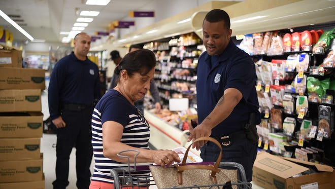 """Yonkers Police Officer, Phillip Yizar provides safety tips on protecting your personal property to shopper at Cross County Mall Stop & Shop after a """"Keep an Eye on Your Purse"""" sticker was placed on her bag by a People's United Bank representative."""