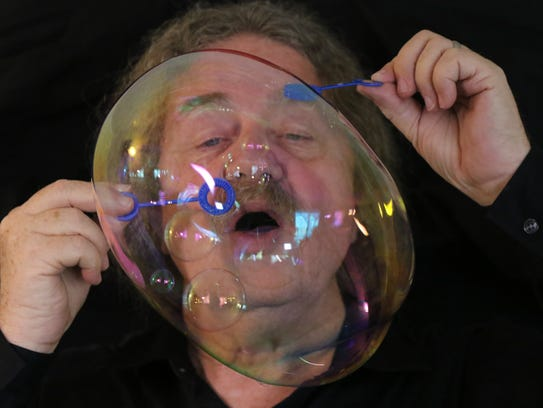 """Tom McAllister blows a """"galaxy"""" bubble, in which smaller"""
