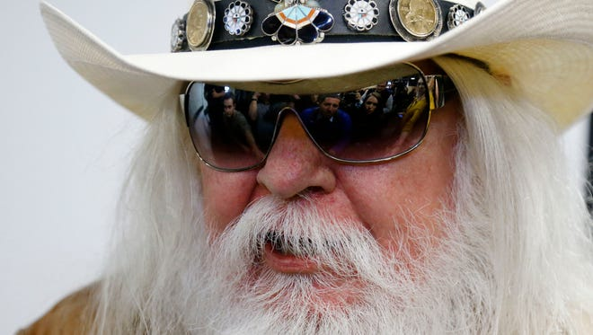 FILE - In this Jan. 29, 2013, file photo, reporters are reflected in the sunglasses of Leon Russell as he answers a question at a news conference in Tulsa, Okla. Russell, who sang, wrote and produced some of rock 'n' roll's top records, has died. (AP Photo/Sue Ogrocki, File)