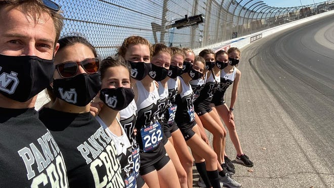 The West Ottawa girls cross country team poses on Michigan International Speedway. The Panthers finished fourth at the state finals.