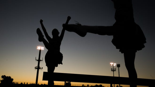 Cheerleaders practice before a football game in  Arizona.