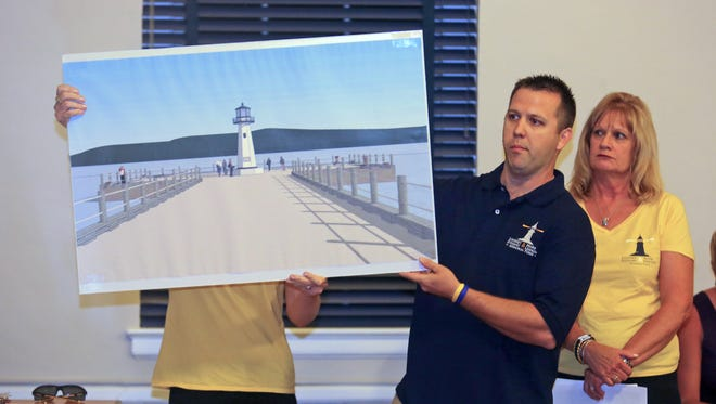Ray Lennon, the brother of Mark Lennon, one of the two people killed in a boat crash on the Hudson River last year, displays a rendering of a proposed lighthouse to be built on the Piermont Pier. Lennon, along with Carol Stewart Kosik, the mother of Lindsey Stewart, the other person killed in the crash, were making a presentation to the Piermont Board of Trustees July 15, 2014, seeking permission to have the lighthouse built as a memorial to the two victims of the boat crash.