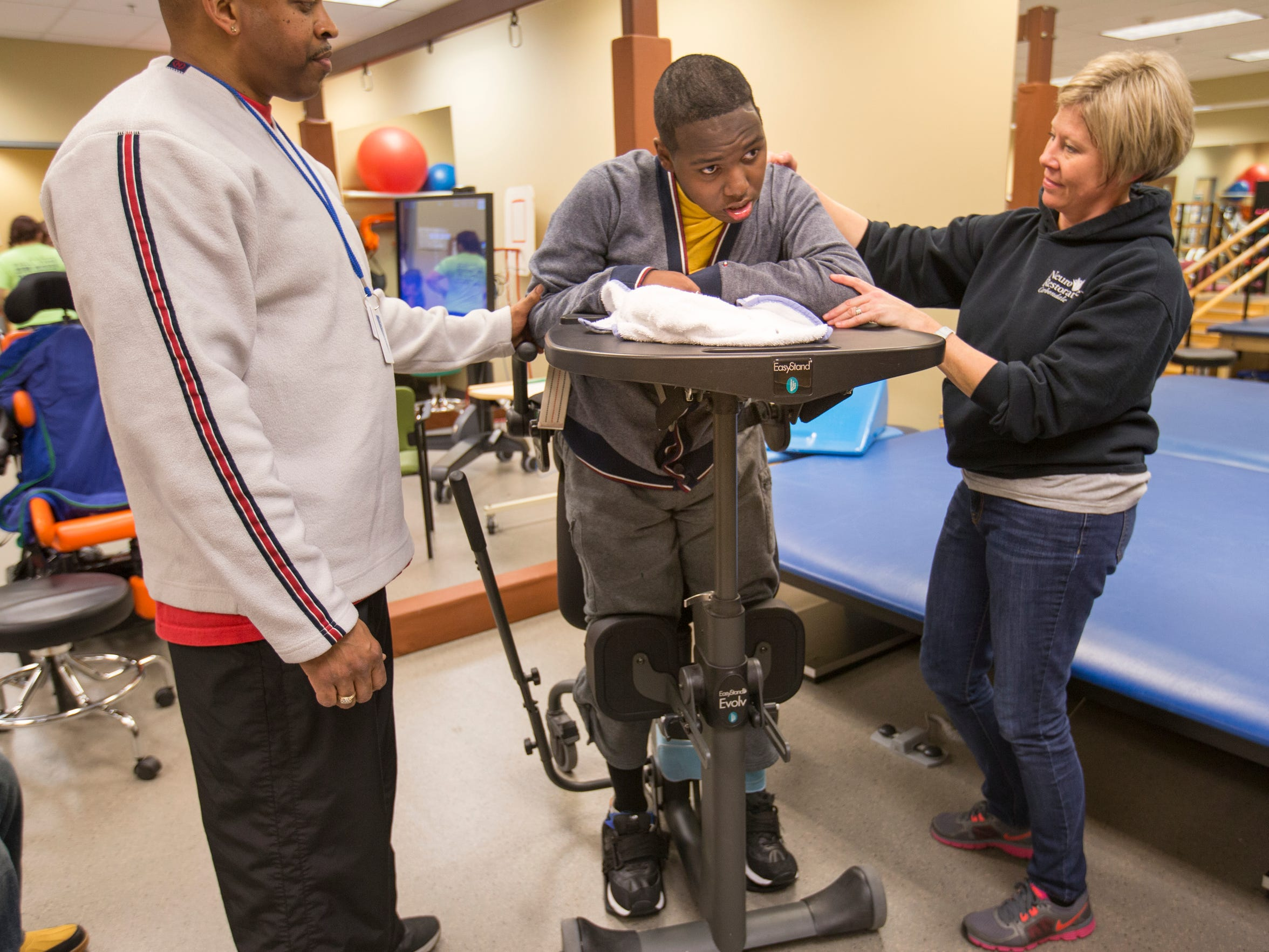 DeAndre Knox is helped by Will Bollinger (left), Carbondale, and Kathy Mileur, Murphysboro, Ill., who work on a device that stretches him into a standing position at Neuro Restorative, Carbondale, Ill., Thursday, January 21, 2016. Knox was shot in 2014, and has a long road of physical therapy ahead.