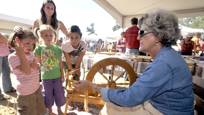 The Guidry family from Crowley, Avia, 5, Cloie, 6, Kaylee, 10, and mom, Erin, watch as Elaine Bourque spins yarn during Festivals Acadiens et Creoles Louisiana Crafts Fair Saturday, Oct. 10, 2010, at Girard Park in Lafayette.