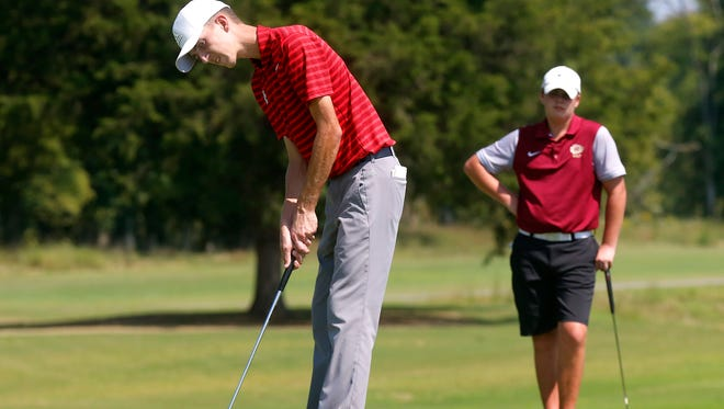 Stewarts Creek's Shelden Barina sinks a putt on the 16th green as Riverdale's Jack Albertson stands behind him  during the 7-AAA District Tournament  on Monday, Sept. 18, 2017, at Old Fort Golf Course.
