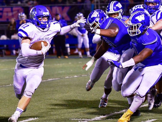 Lakeland's Sean Cullen (left) stiff-arms the Walled