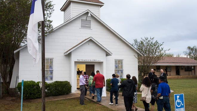 Members walk inside the First Baptist Church of Sutherland Springs to visit the memorial inside on Sunday, Nov. 12, 2017. On Nov. 5, 2017, one week earlier, 25 people and an unborn child were killed in a shooting at the church.