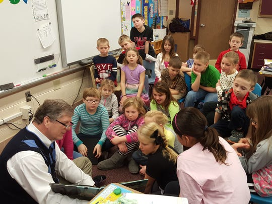 UWSP College of Professional Studies Dean, Marty Loy, shares a book with elementary students.