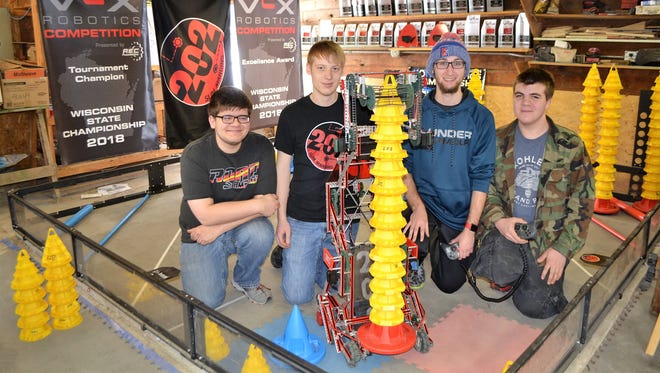 The 202 Slim Margins team is seen with their robot, Darren 3, at their  Abrams workshop. From left is team mentor Jake Sellhausen, and team members Kelton Lepak, Jacob Delzer and Jordan Sellhausen. They are kneeling inside a regulation VEX Robotics area they set up to practice on. Behind them are the two banners for winning the VEX Robotics state tournament this month and the competition's Excellence Award, which recognizes their overall quality of their of their work. Behind them on the right are trophies for winning regional matches.