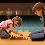 Jada Dusek, left, and Abby Miller play a game of checkers using chess pieces during a Big Brothers Big Sisters of Great Falls school-based program at West Elementary School. BBBS is recruiting high school students and adults to serve as mentors for the 2015-2016 school year.
