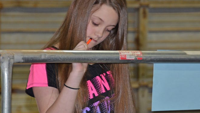 Sarah Dickerson, 11, of Hartsville ponders a response on a judging score sheet during the annual Central District 4-H Livestock & Meats Judging Contest April 5 in a Tennessee Livestock Center small animal arena.