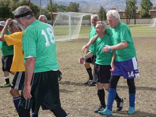 The green team celebrates their win over the yellow team in a 75-and over-soccer match in Palm Desert, February 8, 2017.