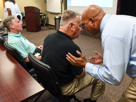 Anderson County Administrator Rusty Burns, left, listens