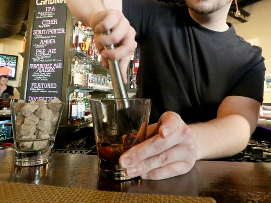 Bar Manager Adam Nobs muddles a raw sugar cube, bitters, a Louxardo marinated cherry and orange slice in Pewaukee's Artisan 179 version of the classic Old Fashion that the call Ron and Mary's Brown Mumbler.