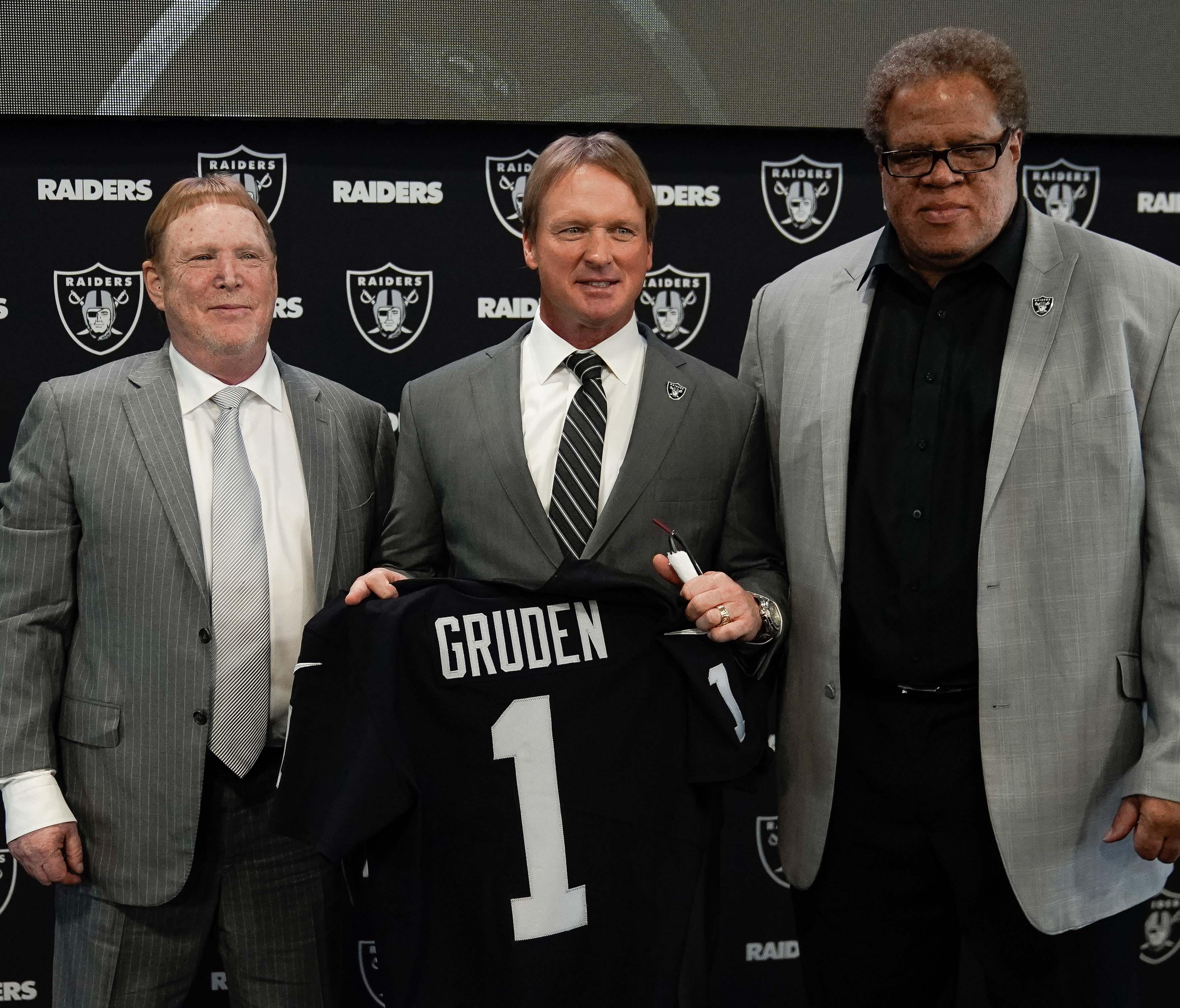 Oakland Raiders owner Mark Davis, head coach Jon Gruden, and general manager Reggie McKenzie pose for photos after a press conference.