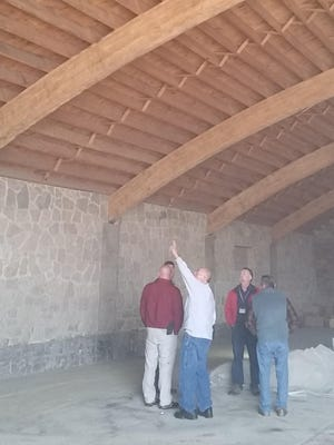 Door County Supervisor Dan Austad, a member of the County Board Property Committee, points out timber arch roof trusses that are to remain exposed in an area of the former Door County Highway Department shop in Sturgeon Bay being converted to the dining area of a new senior citizens center. Also pictured are, from left, committee member Jon Koch, Door County Building and Grounds Director Wayne Spritka, committee member Steven Sohns and committee chairman Richard Virlee.