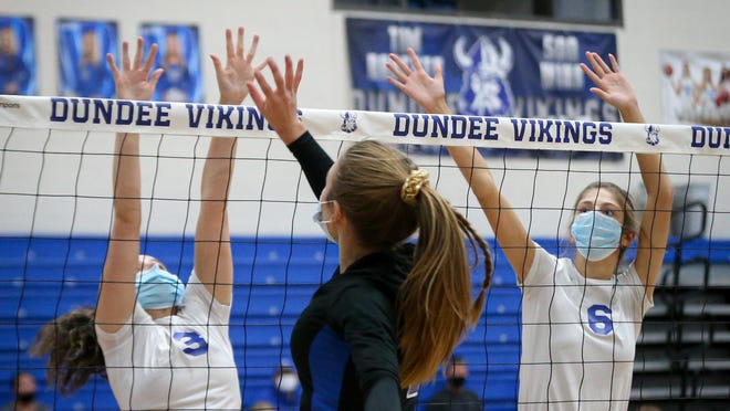 Dundee's Morgan White (left) and Mylee Salenbien go up to block of Ida's Taylor Parker during a quad meet Thursday at Dundee High School.
