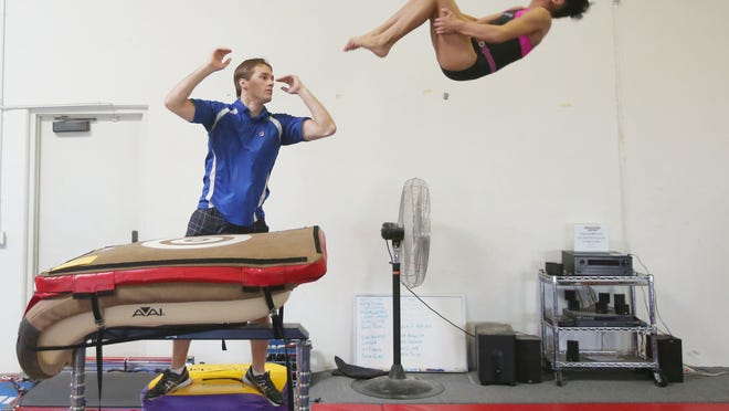 Tegan Nguyen is a 9 year old gymnast, ranked as one of the top 100 in the country for her age group. In this photo she practices coach Nick Hobson one of her two daily routines at  Power Kids Center.