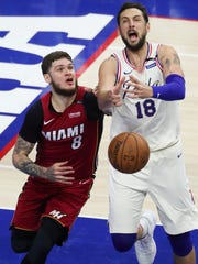 Miami's Tyler Johnson (left) fouls Sixer Marco Belinelli for his sixth foul in the second half of the Sixers' 104-91 win in game five of an opening round playoff series at the Wells Fargo Center in Philadelphia Tuesday.