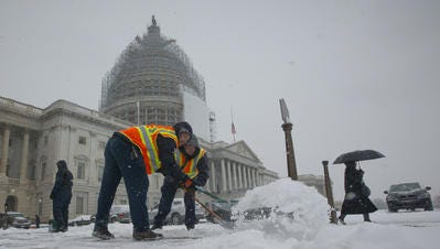 Workers clear the sidewalks outside the US Capitol Building in Washington, Tuesday, Jan. 6, 2015.