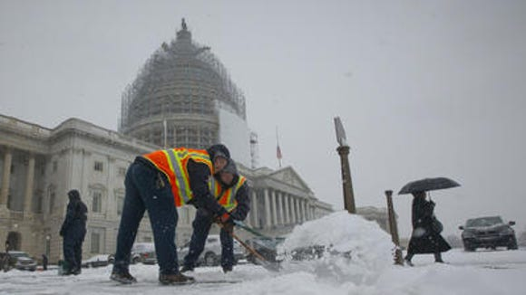 Workers clear the sidewalks outside the US Capitol