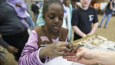 Nya Wright, 8, Indianapolis, takes a look at a whip scorpion held by entomologist Ronda Hamm, at Passport to Hi-Tech at Conner Prairie, Fishers, Saturday, March 5, 2016. The event matches more than a thousand kids with professionals who expose them to a variety of technical and scientific disciplines.