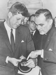 Rev. Theodore M. Hesburgh, C.S.C., at age 44, (right)  and President John F. Kennedy examine the Laetare Medal together in the Oval Office in 1961.