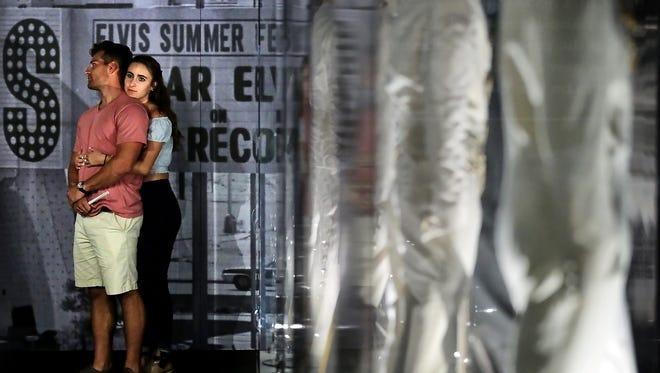 Elvis fans wander through a forest of jumpsuits at Graceland's Elvis the Entertainer Museum.