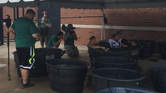 Linebacker Chris Frey (23) and three of his MSU teammates relax in a cold tub as Big Ten Network TV crews film them following the Spartans' first practice of the season on Saturday in East Lansing.