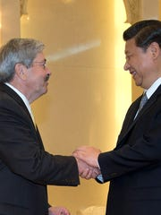 Iowa Gov. Terry Branstad, left, is greeted by Chinese