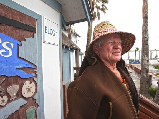Ernie Buttler, owner of Snoopy's Pier restaurant and Scoopy's ice cream shop, looks across his parking lot at Marker 37 Marina, which he built in the 1980s. All three the structures he built survived, though parts of the exteriors were damaged heavily.