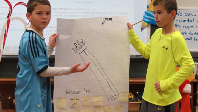 Old Mill Elementary fourth graders Will Brangers, left, and Brandon Mudd discuss a design for a prosthetic arm.