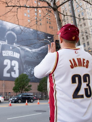 Fans take pictures of a mural of LeBron James in Cleveland