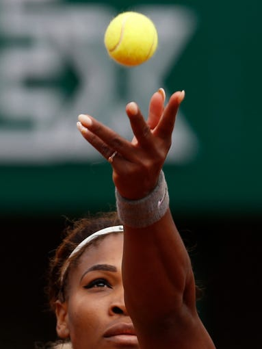 Serena Williams of the U.S, serves to France's Alize Lim.
