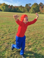Theo Halko, 10, raises his hands in the air during practice for Let Me Run, a holistic health program that uses running as a vehicle to break down destructive male stereotypes.