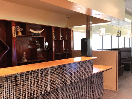 Emperor's Buffet & Grill's front desk and seating area are done in earth tones and neutral colors.