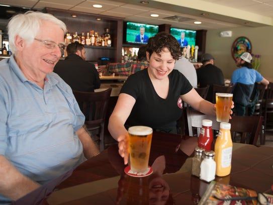 Waitress Haleigh Bunting serves a beer to John McCloskey