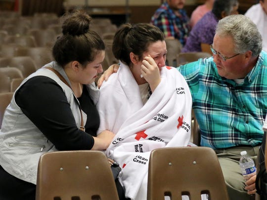 Hannah Miles, center, is reunited with her sister Hailey Miles, left, and father Gary Miles, right, after a shooting at Umpqua Community College in Roseburg, Ore., on Thursday, Oct. 1, 2015.   (AP Photo/Ryan Kang)