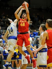 Castle's Brandon Eades (14) blocks a shot from Mater Dei's Sam Fulton (40) during the first round of the SIAC Tournament at Castle High School in Newburgh, Tuesday, Jan. 10. 2017. Castle beat Mater Dei 78-41.