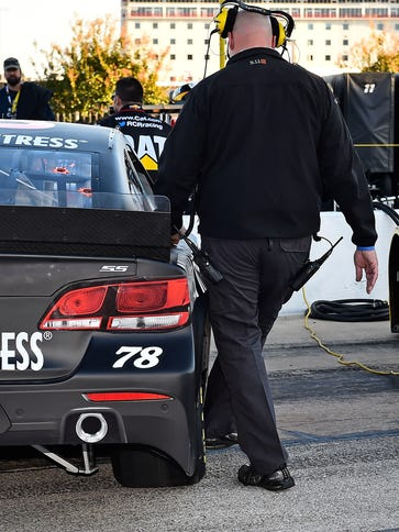 A NASCAR Official bends the side skirt back into place