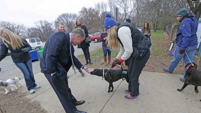 Indianapolis Mayor Joe Hogsett gets a sniff from Millie, owned by Taylor Jacoby, right, during Indy Parks community celebration at the Broad Ripple Dog Park. The event thanked dog park customers, contest supporters and the community on Dec. 3, 2016.