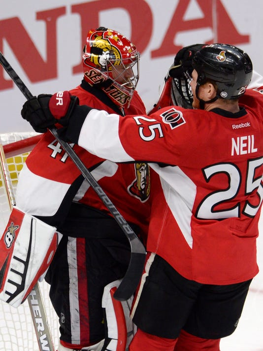 Ottawa Senators goalie Craig Anderson and Chris Neil celebrate defeating the Montreal Canadiens in Game 4 of an NHL hockey first-round playoff series, Wednesday, April 22, 2015 in Ottawa, Ontario. The Senators beat the Canadiens 1-0. (Adrian Wyld/The Canadian Press via AP)  MANDATORY CREDIT